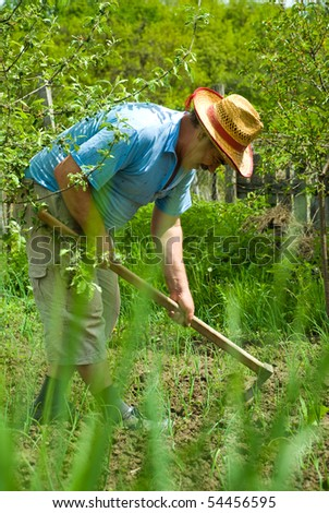 Portrait of happy peasant digging in the garden soil with spring onions at country