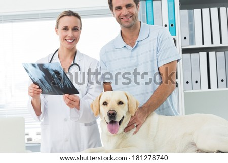 Portrait of happy pet owner and veterinarian with Xray of dog in hospital