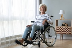 Portrait of happy positive handicapped old woman sitting in wheelchair feel optimistic at home or retirement house, smiling senior disabled female in invalid carriage wheel chair look at camera
