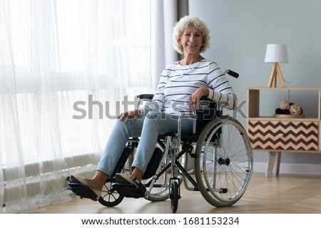Portrait of happy positive handicapped old woman sitting in wheelchair feel optimistic at home or retirement house, smiling senior disabled female in invalid carriage wheel chair look at camera Photo stock ©