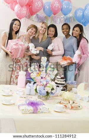 Portrait of happy pregnant woman and female friends at a baby shower