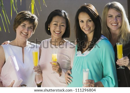 Portrait of happy pregnant woman with friends holding drinks