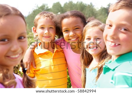 Portrait of happy preschoolers looking at camera while embracing