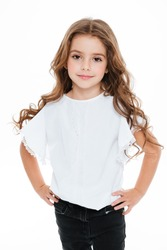 Portrait of happy pretty curly little girl standing and posing over white background