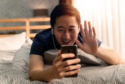 Portrait of happy 30s aged Asian man making facetime video calling with smartphone at home. He's waving on phone screen. Using conferencing meeting online app, social distancing, concept