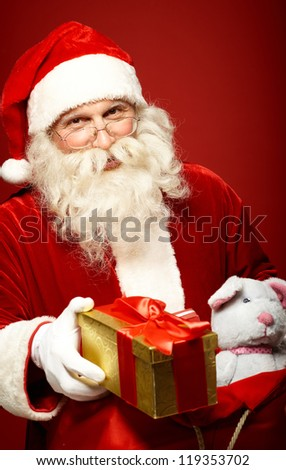 Portrait of happy Santa Claus giving Christmas present