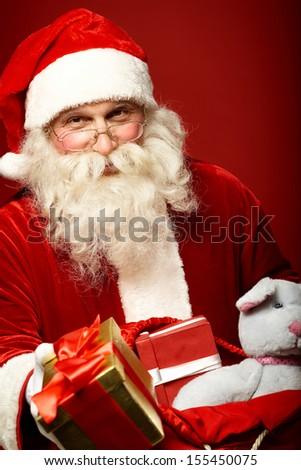 Portrait of happy Santa Claus giving Christmas present