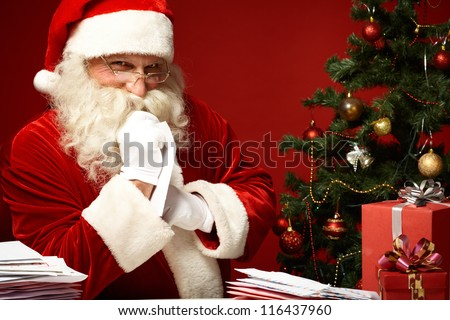 Portrait of happy Santa Claus looking at camera with pile of letters near by