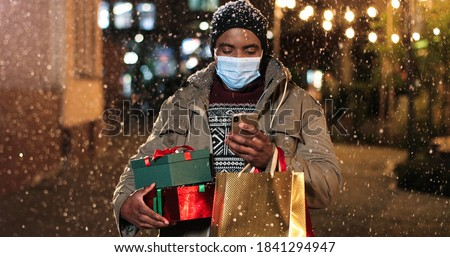 Portrait of happy satisfied African American man standing and texting on mobile phone while buying online. Male with shopping bags paying on smartphone with credit card while snowing. Presents concept