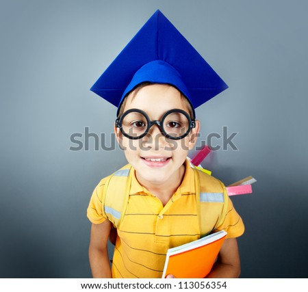 Portrait of happy schoolboy with copybooks looking at camera