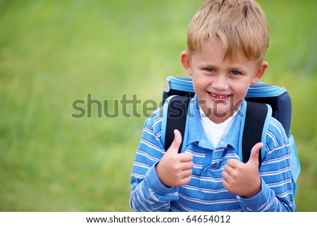 portrait of happy schoolboy with satchel on his back