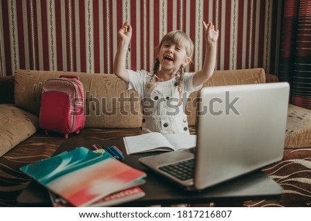 Portrait of happy schoolgirl child doing homework at home on a laptop. Distance learning, home learning via the Internet. Knowledge is power. Little girl writes homework in a notebook, reads a book.
