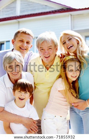 Portrait of happy senior and young couples looking at camera outdoors with new cottage at background
