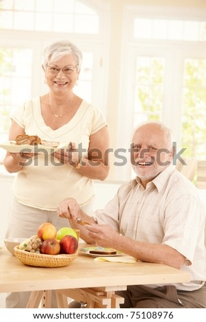 Portrait of happy senior couple at breakfast table in bright kitchen, smiling at camera.?