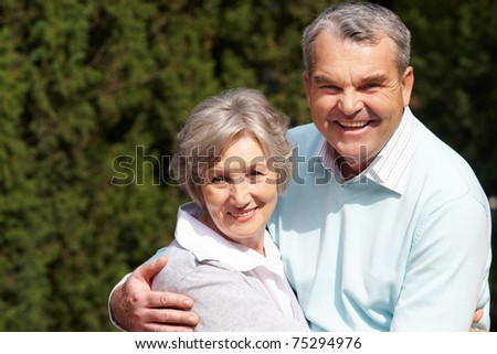 Portrait of happy senior couple embracing each other and looking at camera