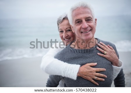 Portrait of happy senior couple embracing each other on the beach