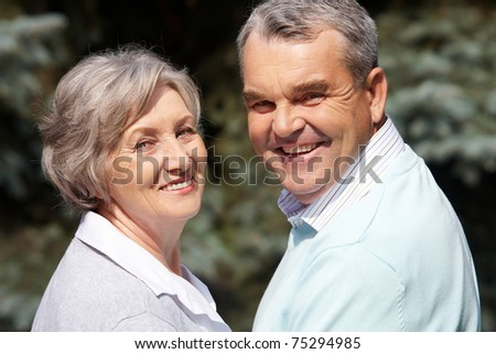 Portrait of happy senior couple looking at camera on sunny day