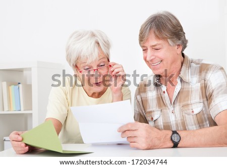 Portrait Of Happy Senior Couple Reading Letter Together