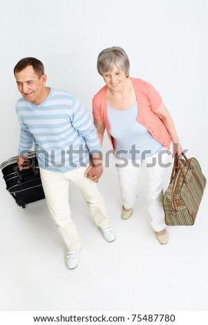 Portrait of happy senior couple with baggage
