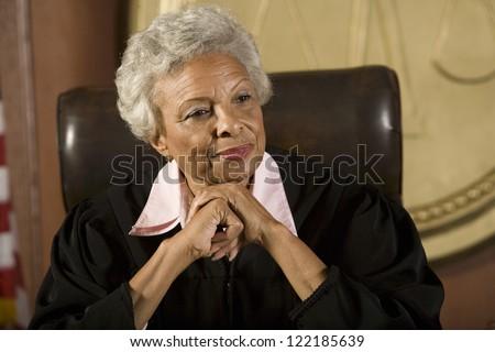 Portrait of happy senior judge sitting in courtroom
