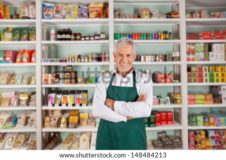 Shutterstock Portrait of happy senior male owner standing arms crossed against shelves in supermarket