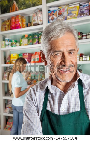 Portrait of happy senior male owner with female customer shopping in background