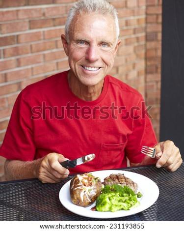 Portrait of smiling senior man eating strip steak served