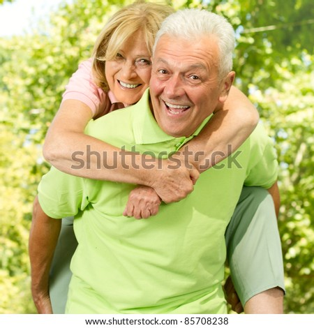 Portrait of happy senior man giving piggyback ride outdoors.