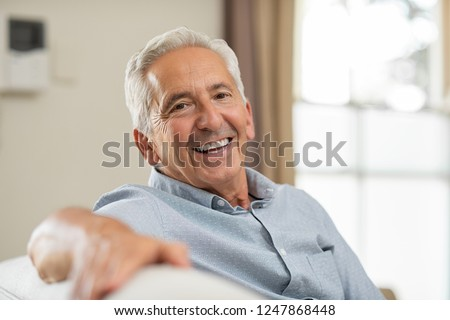 Portrait of happy senior man smiling at home. Old man relaxing on sofa and looking at camera. Portrait of elderly man enjoying retirement.