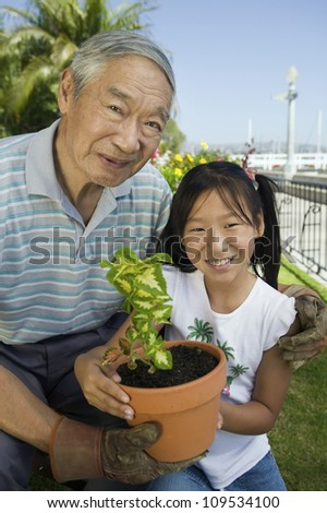 Portrait of happy senior man with granddaughter gardening together