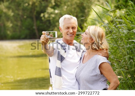 Portrait of happy senior people standing at lakeside while elderly man taking self portrait with his mobile phone.