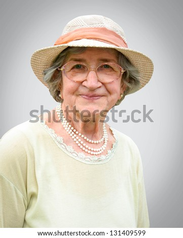Portrait of happy senior woman against gray background