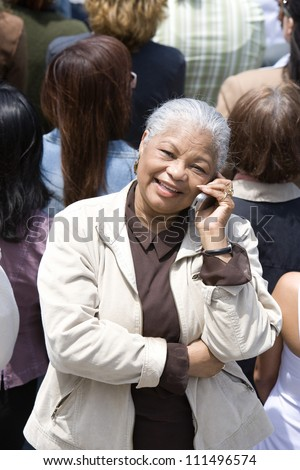 Portrait of happy senior woman communicating on mobile phone with people in the background