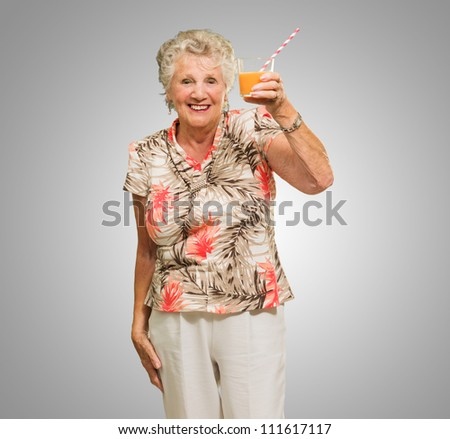 Portrait Of Happy Senior Woman Holding, Orange Juice Glass Isolated Over Green Background