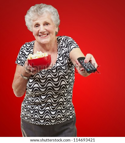portrait of happy senior woman looking the tv over red background - stock photo