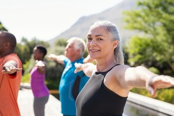 Portrait of happy senior woman practicing yoga outdoor with fitness class. Beautiful mature woman stretching her arms and looking at camera. Portrait of smiling ladywith outstretched arms at park.