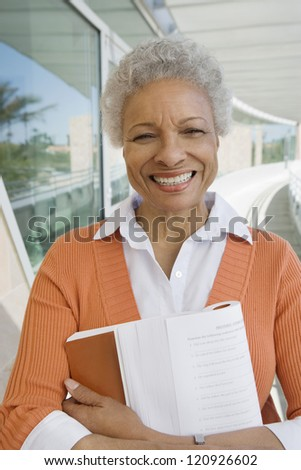 Portrait of happy senior woman standing with book