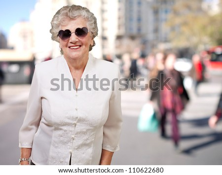 portrait of happy senior woman wearing heart glasses at street