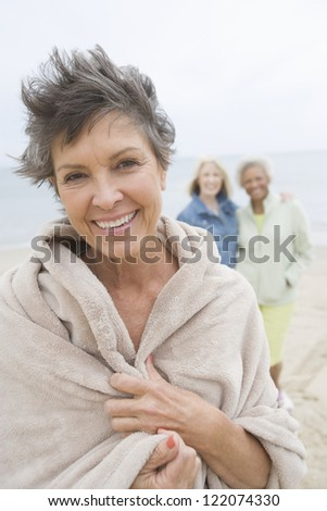 Portrait of happy senior woman with blanket and friends in the background