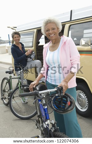 Portrait of happy senior women with bicycles and RV