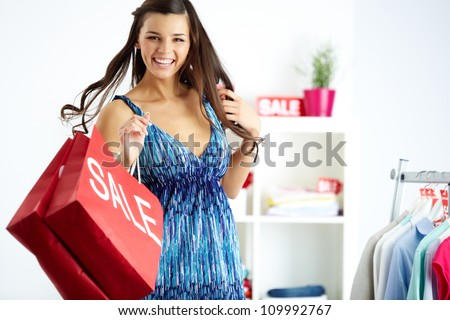 Portrait of happy shopper with bags laughing in clothing department