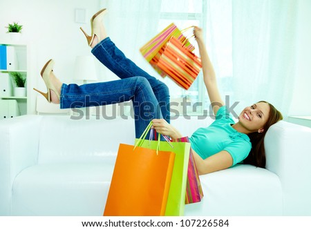 Portrait of happy shopper with paperbags lying on sofa and looking at camera
