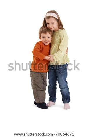 Portrait of happy siblings hugging each other, smiling at camera.?