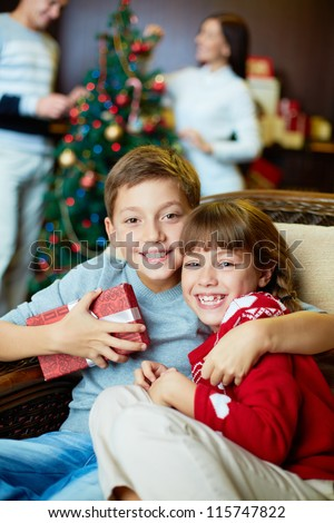 Portrait of happy siblings looking at camera on xmas eve with their parents on background