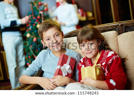 Portrait of happy siblings with giftboxes on Christmas evening