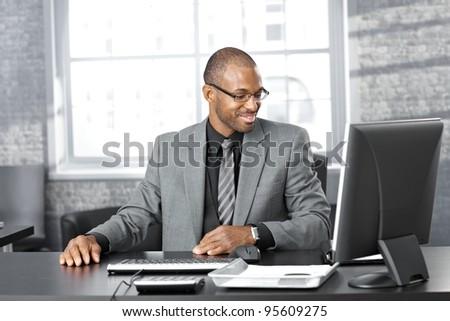 Portrait of happy smart black businessman sitting at desk in office, smiling.?