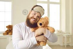 Portrait of happy smiling adult grown up man with ginger mustache and beard, in white pajamas and sleep mask on head, tenderly cuddling cute teddy bear and looking at camera. Childish behavior concept