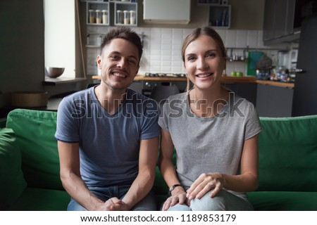 Portrait of happy smiling affectionate young couple, family, man and woman sitting near together on couch, sofa at home, look at camera