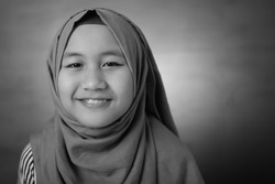 Portrait of happy smiling Asian muslim girl, close up image, monochrome black and white portrait