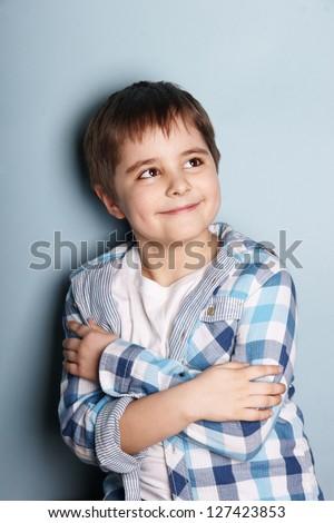 Portrait of happy smiling beautiful boy looking up, studio shot